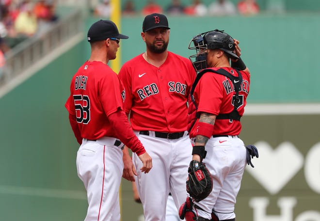 """Red Sox pitching coach Dave Bush, left, speaks with pitcher Brian Johnson, center, and catcher Christian Vazquez during a spring training game in Florida on March 10. Bush says of this lost season: """"It's been frustrating for all of us involved. We all want to win."""""""