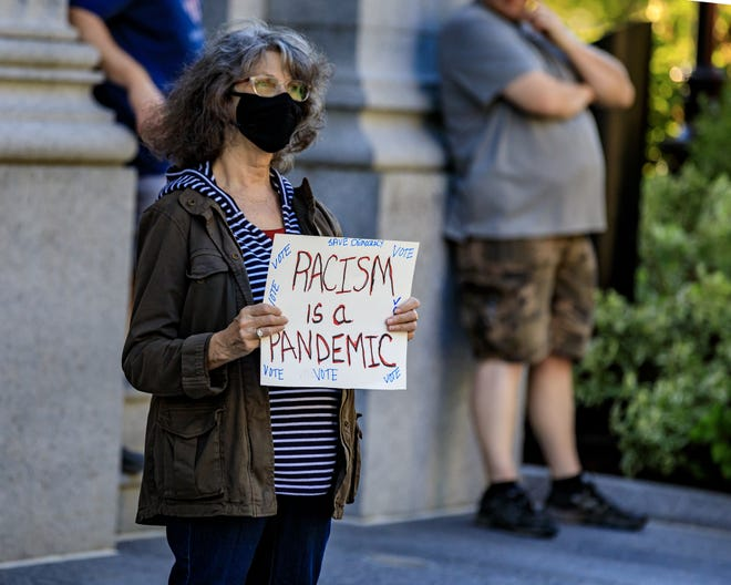 """A protestor holds a sign that reads """"Racism is a Pandemic,"""" during a Black Lives Matter rally held at Quincy Square on Sunday, Aug, 30, 2020."""