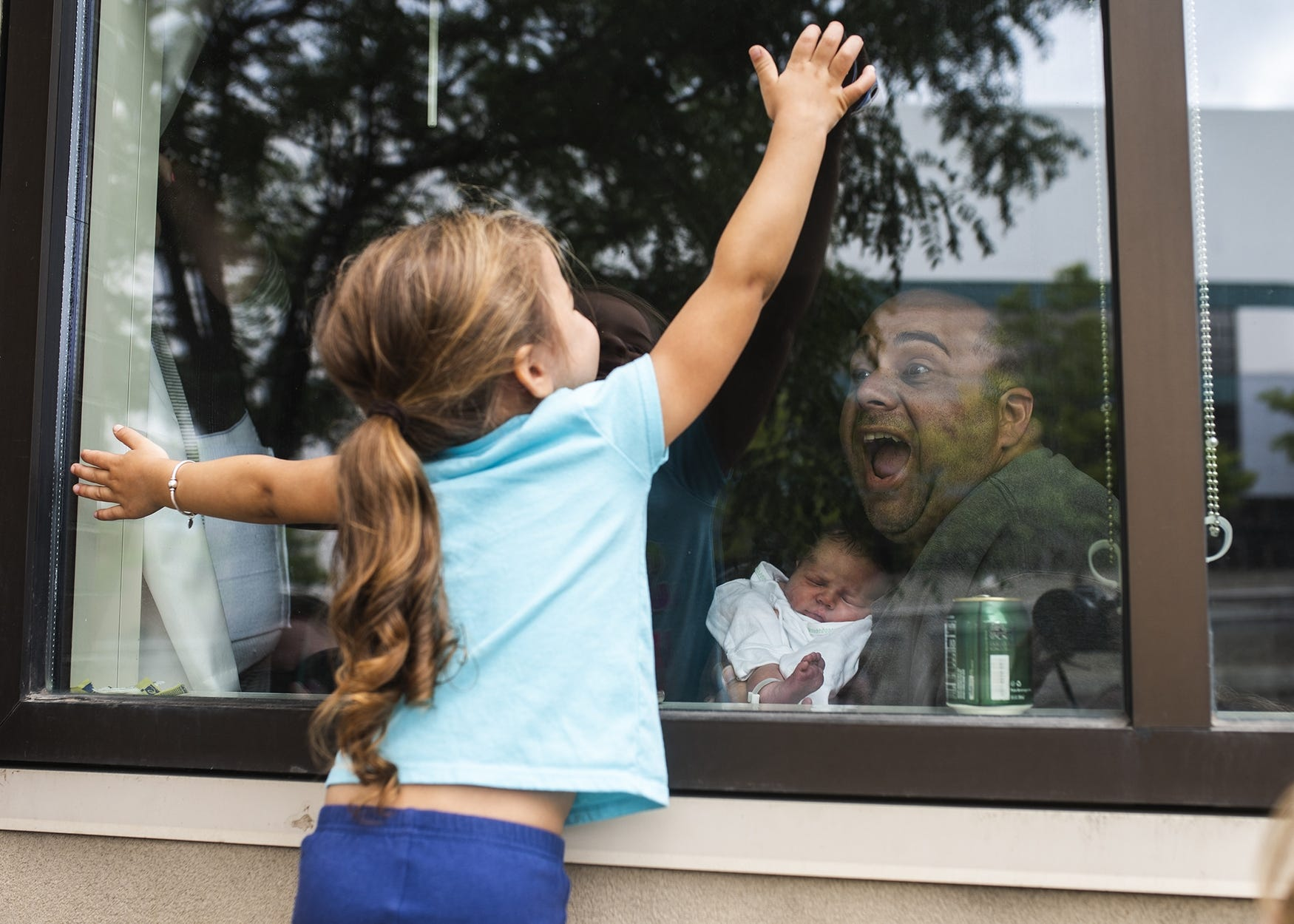 Windows helped make connections: Annistyn Rivera, 3, meets her new baby sister Francesca through the window at St. Vincent Hospital on July 15, 2020.