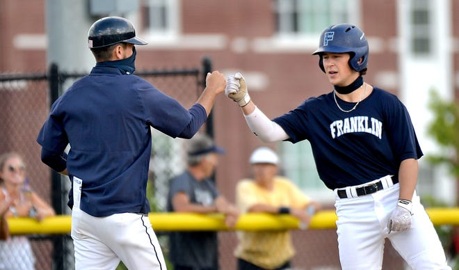 Franklin manager Joe Macchi (left) fist bumps Will Pacheco after Pecheco reached third base during a game against Northborough last summer at Franklin High School.