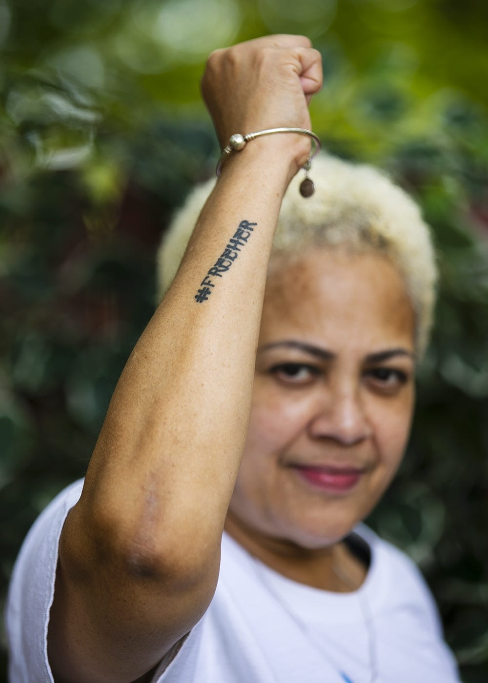 Stacey Borden raises her fist to show her tattoo that reads #FREEHER outside her Brockton home on Tuesday, Aug. 25, 2020. The #FreeHer campaign is part of The National Council's mission to end incarceration of women and girls.