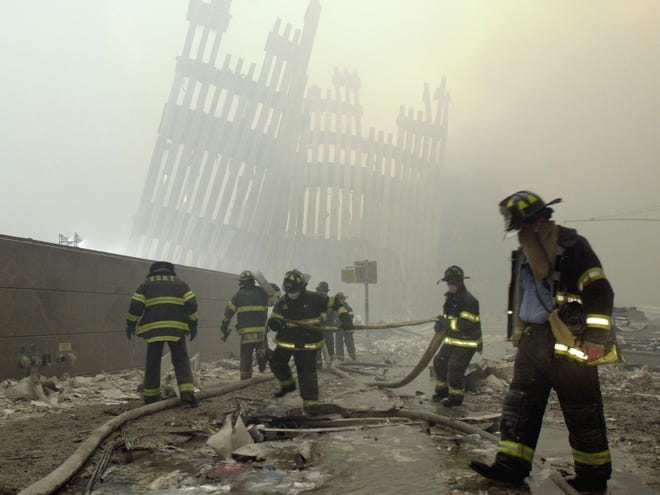 Firefighters work beneath the destroyed mullions, the vertical struts which once faced the soaring outer walls of the World Trade Center towers, after a terrorist attack on the twin towers of lower Manhattan Tuesday, Sept. 11, 2001. As workers cleared some of the rubble, new crews of firefighters and rescue workers charged into the devastation with shovels, pickaxes and flashlights to look for bodies or survivors.