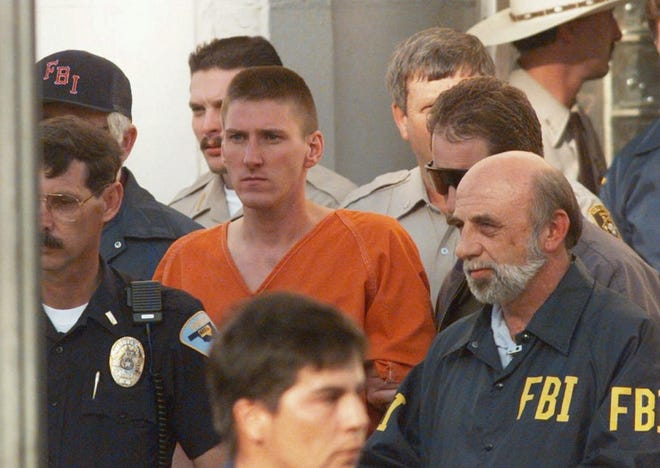 Oklahoma City bomber Timothy McVeigh is escorted by law enforcement officials from the Noble County Courthouse in Perry, Okla., on April 21, 1995. The bombing of the Alfred P. Murray Federal Building on April 19 claimed the lives of 168 people. McVeigh was tried, found guilty and received the death penalty from a jury in Denver on June 13, 1997.