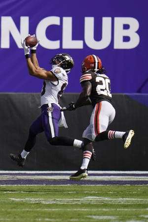 Baltimore Ravens wide receiver Willie Snead, left, catches a touchdown pass ahead of Browns cornerback Tavierre Thomas during the second half Sunday in Baltimore. {Associated Press]