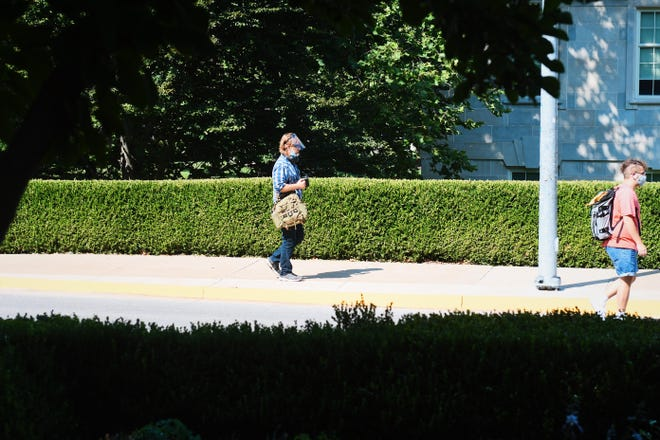 A professor walks to class while wearing a face guard Aug. 24 on the University of Missouri campus.