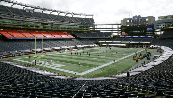 Players warm up to empty seats in Gillette Stadium before Sunday's season-opener between the Patriots and the Dolphins.