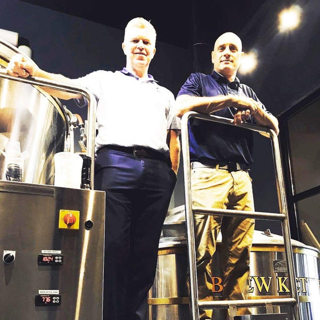 John Melody, left, and Russell Stachewicz, owners of John Russell Brewing Co. Brew House & Restaurant, 7520 Peach St., show off their gleaming new brewing equipment in a July photo illustration. The equipment has already been deployed to make beer, and the restaurant is about 6 weeks away from opening.