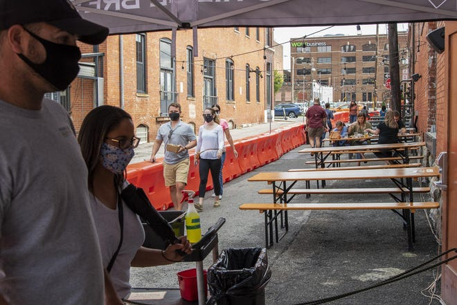 Beer enthusiasts and those eager to share a meal with friends enjoy the newly opened patio at Wolf's Ridge Brewing on North 4th Street Downtown. The city of Columbus is allowing temporary expansion of outdoor seating to help businesses during the coronavirus pandemic.