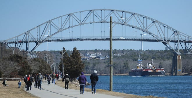 A barge heads under the Bourne Bridge as walkers and others take to the bike trail that runs along both sides of the Cape Cod Canal.