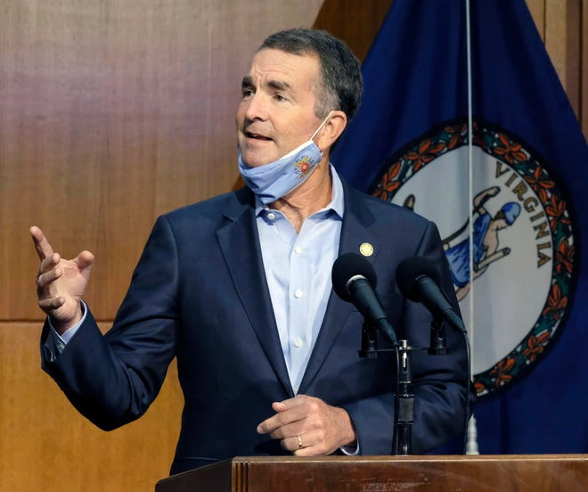 Virginia Gov. Ralph Northam answers a reporter's question during a news briefing inside the Patrick Henry Building in Richmond, Va.