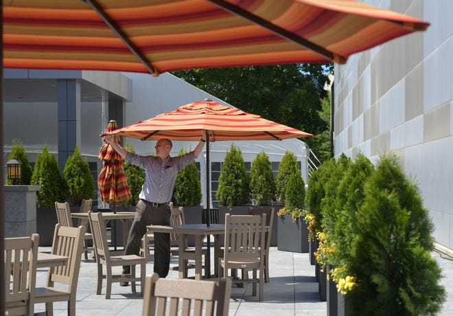 WORCESTER -  Michael Mills, general manager of the 110 Grill on Front Street, opens umbrellas in preparation for outdoor dining  Monday.