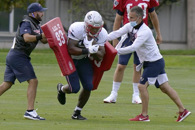 New England Patriots running back Damien Harris runs through a drill during a training camp practice in Foxboro.