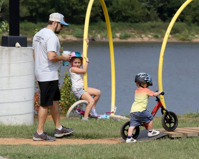 Brett McMillan follows his daughter, Brooklyn, 6, and his son, Samuel, 2, as they ride around the children's bike trail, Saturday, Sept. 19, at the Riverfront Skate and Bike Park.