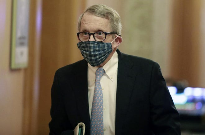 Ohio Gov. Mike DeWine walks into a coronavirus news conference on April 16, 2020 at the Ohio Statehouse in Columbus wearing a mask his wife, Fran, made him.
