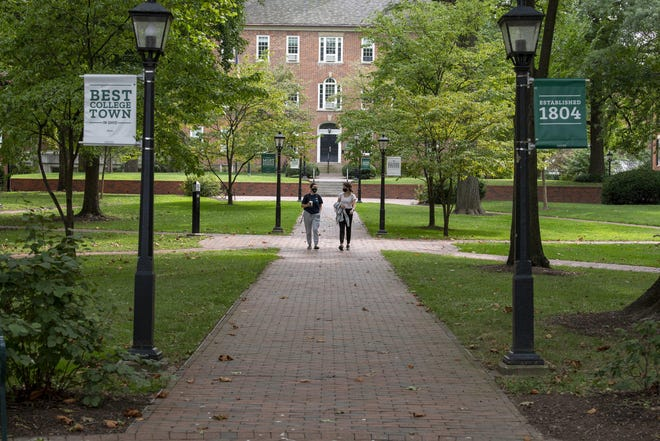 Ohio University seniors, Sophia Evangelisti, left, and Julia Casella, walk through the college green in Athens, Ohio, on Sept. 17, 2020. As part of the first phase, depending on major and needs, some students are permitted to take in-person classes and be part of extracurricular activities at OU. Phase two will be implemented shortly and more students will arrive in dorms and on campus for classes.