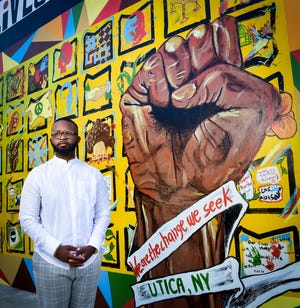 Councilman Delvin Moody stands in front of a Black Lives Matter Mural in Kemble Park in Utica.