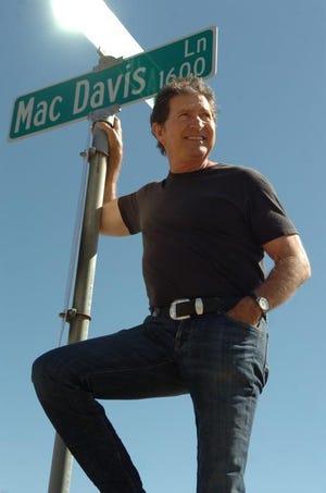 Mac Davis poses by a street sign for Mac Davis lane in Lubbock.