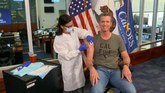 California Gov. Gavin Newsom, shown here, who was vaccinated against the flu on Sept. 28, is taking in more heat than his recent evening order.