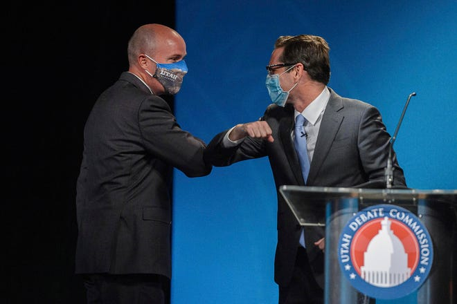 Republican Lt. Gov. Spencer Cox, left, and Democrat Chris Peterson, rivals to become Utah's next governor, bump elbows after facing each other in a prime-time debate in Salt Lake City in 2020.