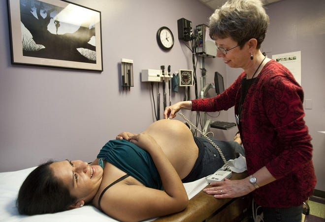 Nurse practitioner Peggy Wall visits with patient Leticia Martinez in 2011. People's Community Clinic will focus its $25,000 St. David's Foundation grant for work in communities around perinatal care.