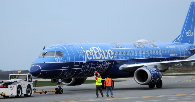 The first JetBlue flight to New York City gets a signal from the ground crew on the runway at Worcester Airport on May 3, 2018.