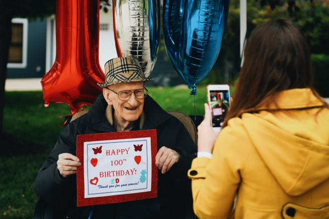 Ed McComb poses for a photo with a sign made for him by a neighbor on his 100th birthday. McComb was honored with a celebratory drive-by from friends, family, and members of the community in early October in Columbia.
