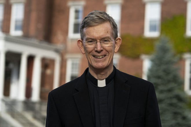 The Rev. Philip L. Boroughs, S.J., president of Holy Cross, stands in front of O'Kane Hall Friday on the college's campus.