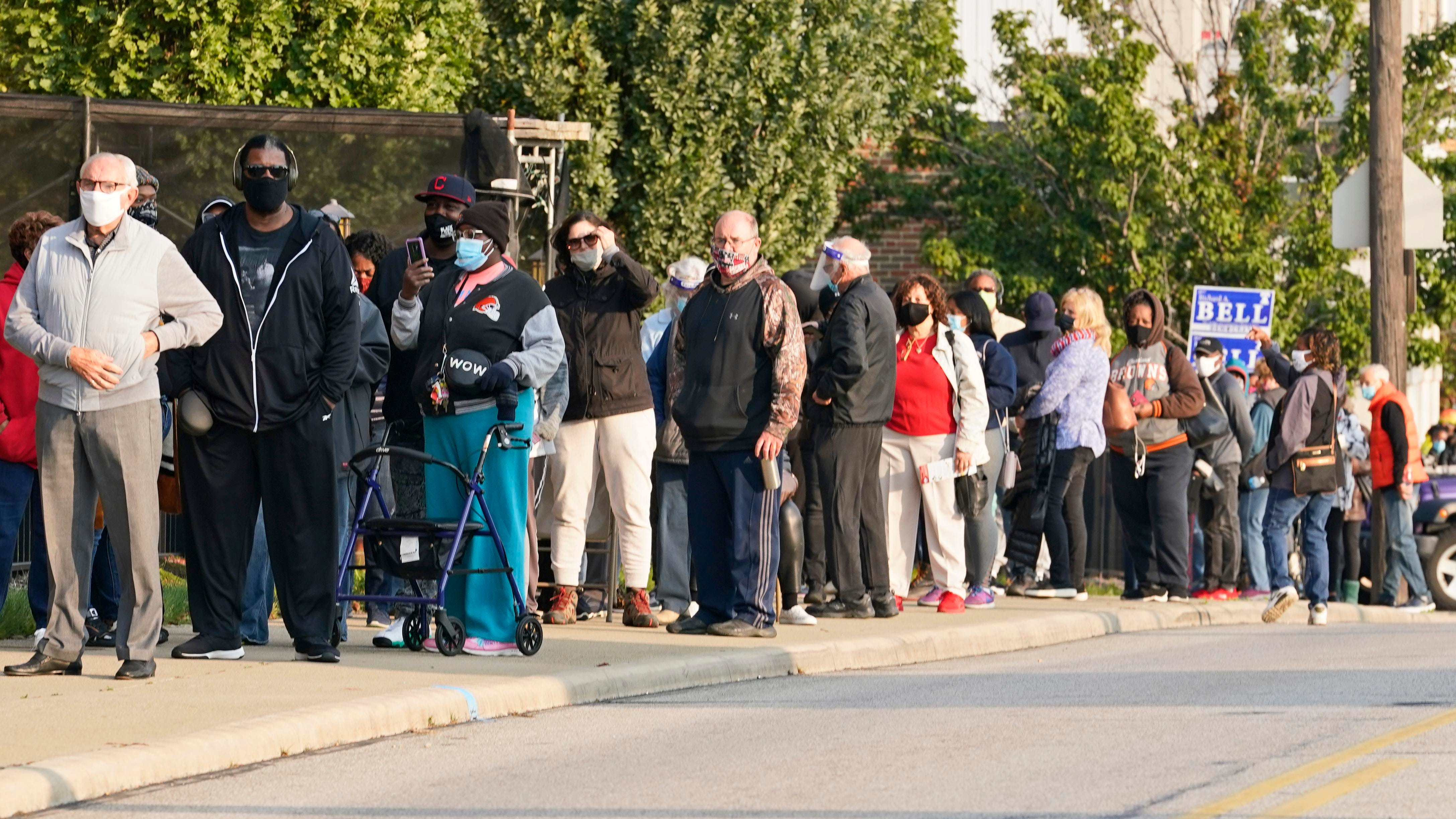 Long lines of people wait outside of the Cuyahoga County Board of Elections to participate in early voting Tuesday in Cleveland.