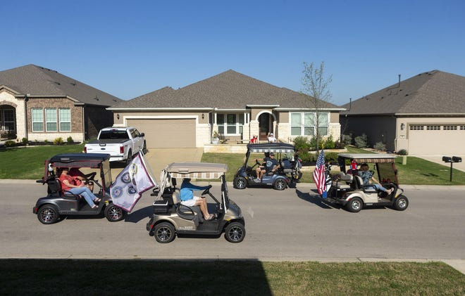 Golf cart traffic is heavy during a March parade in Sun City Texas. State Attorney General Ken Paxton has been asked for an official opinion on whether driver's licenses are required to operate golf carts on public streets where they are legal.