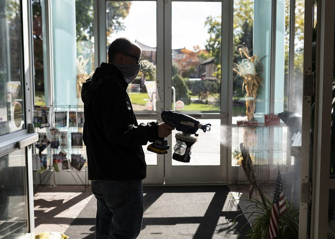 WORCESTER - Andrew Carelli sanitizes doors during early voting hours at the Worcester Senior Center on Oct. 17.