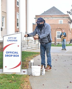 "Jason Komberg places his ballot in a secure drop box outside Gardner City Hall as Scott M. Graves plays ""Yankee Doodle."""
