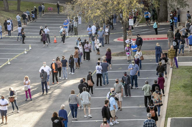 People wait in a long line to vote at a polling place set up at the Renaissance Austin Hotel on Oct. 13, the first day of early voting in Texas for the 2020 presidential election.
