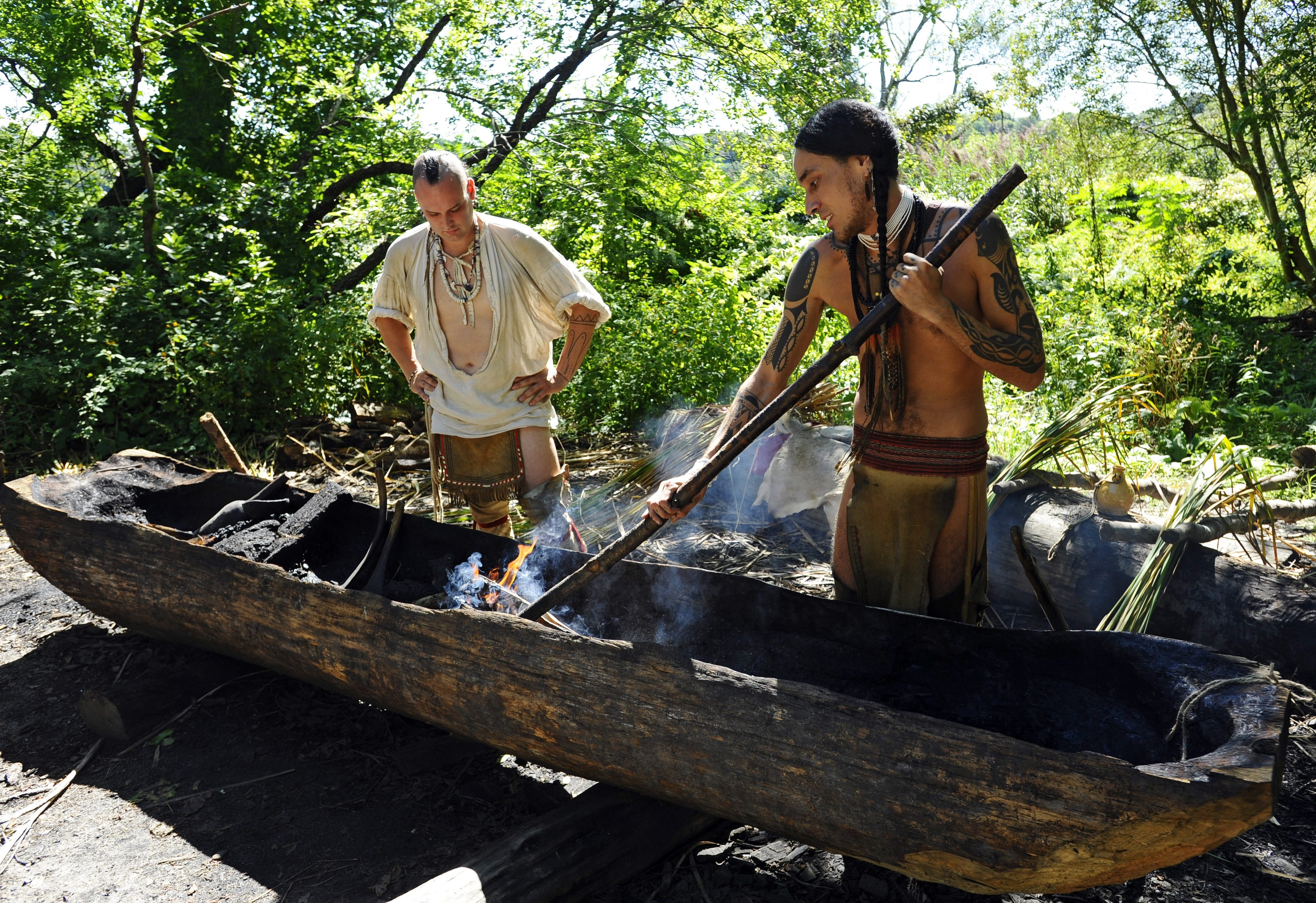 Mashpee Wampanoag and Plimoth Patuxet site supervisor Phillip Wynne, RIGHT, scrapes out a pine mishoon while Dan Shears observes. Plimoth Patuxet is a living museum that has a replica 17-century Pilgrim village and Wampanoag settlement.
