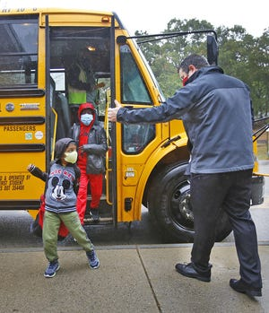Principal Pat Higgins directs students arriving on the bus for the first day of in -person lessons in Weymouth on Tuesday, Oct. 13, 2020.