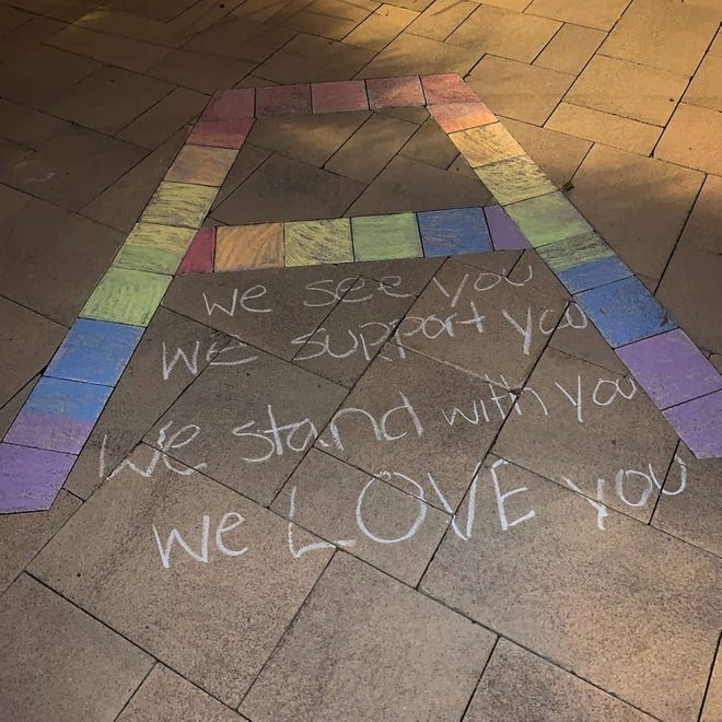 Assumption College students wrote messages of support in chalk on the sidewalks on the Worcester campus Saturday. The students say a campus police officer stopped them from writing the messages, but a school spokesman called the incident a misunderstanding.
