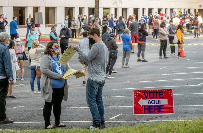 People wait in a long line to vote at an early voting location at the Renaissance Austin Hotel on Oct. 13, the first day of early voting.
