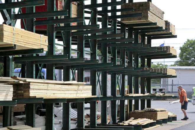 Pressure-treated lumber sits on racks at a lumber yard. Recycling this type of wood is not possible in local programs because of toxins and reuse is limited. Reducing its use or maintaining it can be way to keep it from disposal.