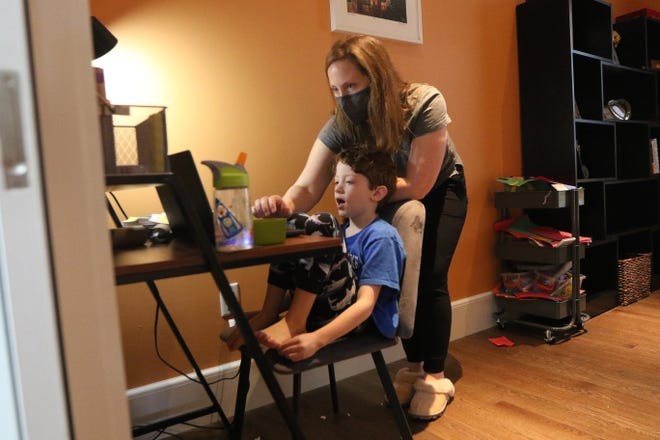 Cambridge second-grader Jed Barrett, 7, gets some help with remote learning from his mom, Norma, on Wednesday afternoon, Oct. 21.
