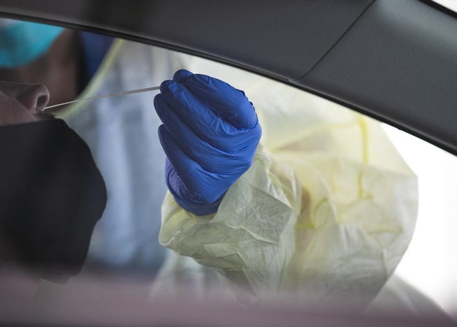 Brockton Neighborhood Health Center nurse practitioner Kelly Nagi swabs a patient in their vehicle at the drive-thru coronavirus testing site at Brockton High School on Wednesday, July, 29, 2020. The Brockton Neighborhood Health Center, through the Department of Public Health's Stop the Spread initiative, is offering free COVID-19 testing to asymptomatic residents of Brockton and surrounding communities through Sept. 12 by appointment only from noon to 7 p.m. on Mondays and Thursdays and 9 a.m. to 4 p.m. on Wednesdays.