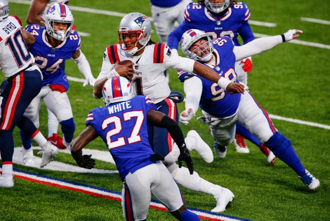 New England Patriots' Cam Newton (1) rushes past Buffalo Bills' Harrison Phillips (99) and Tre'Davious White (27) during the second half of an NFL football game Sunday, Nov. 1, 2020, in Orchard Park, N.Y. Newton fumbled the ball on the play. The Bills won 24-21.