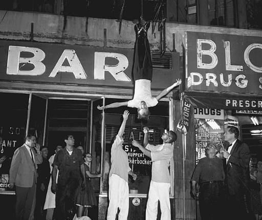 """Magician James Randi, an escape artist from Toronto, Canada, appears on the CBS-TV show """"It's Magic"""", at 65th Street and Broadway in New York City on Sept. 4, 1955. Attendants get set to grab Randi, who was tied up in a strait jacket loaned by one of New York's hospitals and hoisted up six stories upside down and hanging about 65 feet up before his escape in 2 1/2 minutes."""