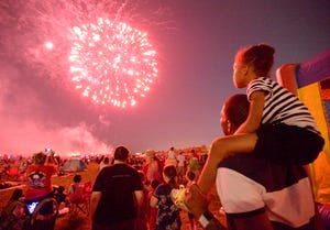 Nigel Willis holds his daughter, Giselle Willis, 6, on his shoulders as they watch the fireworks during Fort Gordon's Annual Independence Day celebration Thursday evening July 3, 2014.