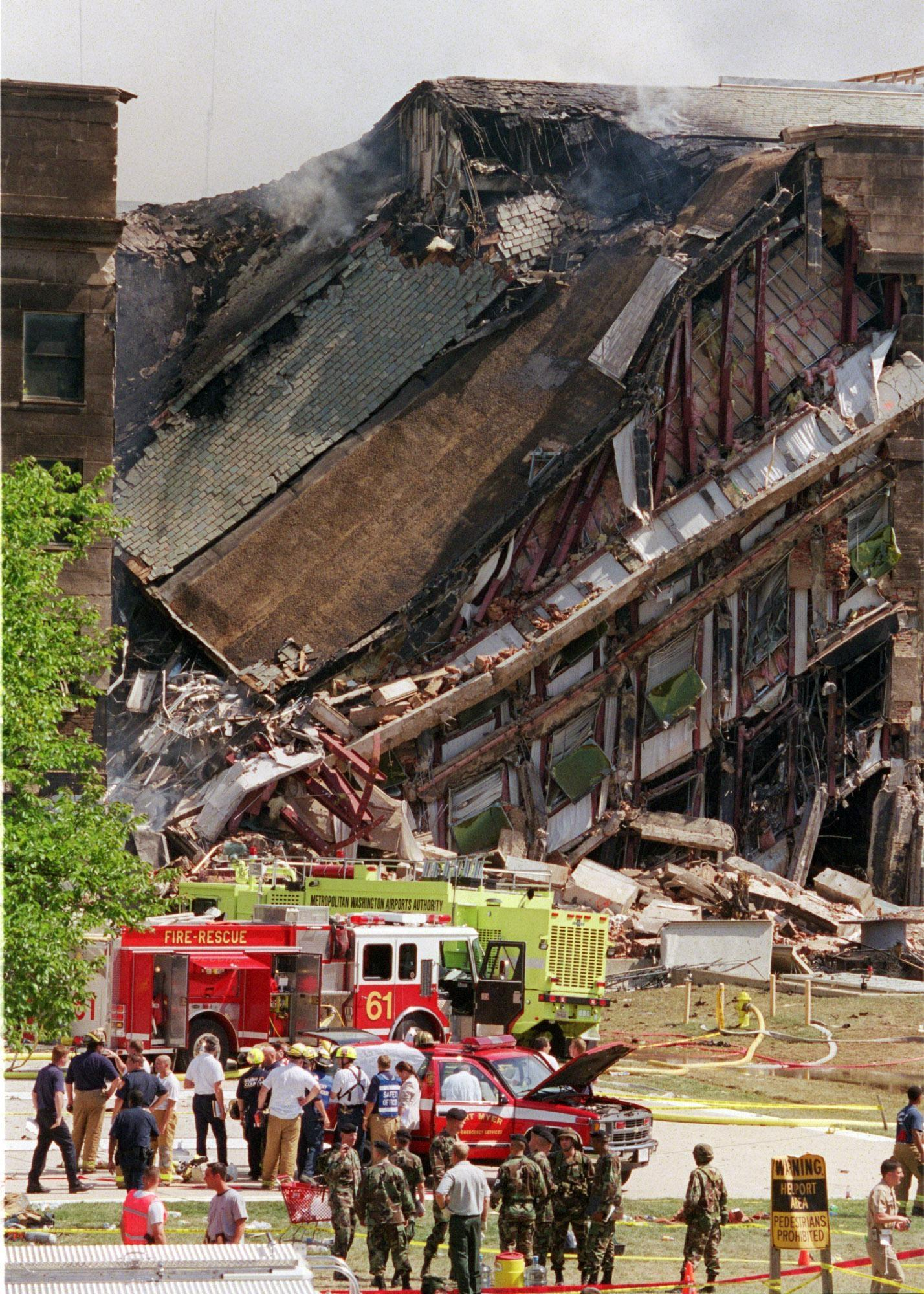Rescue workers look over damage at the Pentagon Tuesday, Sept. 11, 2001. The Pentagon burst into flames and a portion of one side of the five-sided structure collapsed after the building was hit by an aircraft in an apparent terrorist attack.