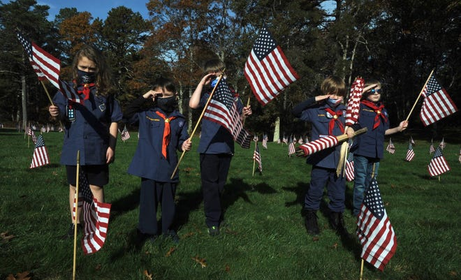 Cub Scouts from Pack 11 in Plymouth pause from flag planting for a flag salute at the Bourne National Cemetery in November 2020, where a large group of volunteers showed up to place flags on all the graves to honor them for Veteran's Day. {File Photo]