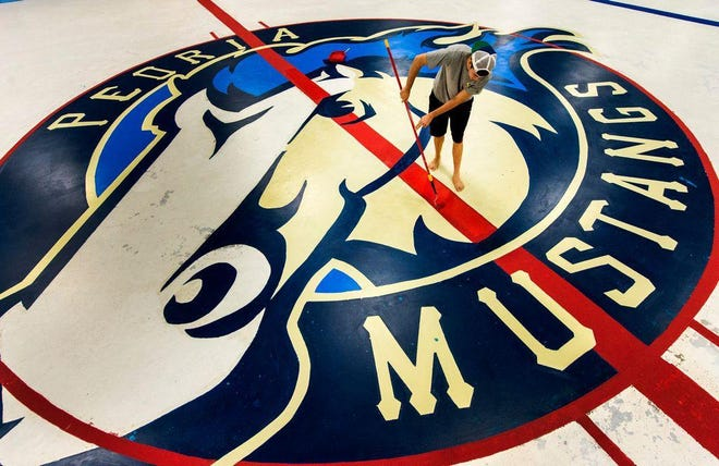 An employee at Owens center paints a red stripe atop the Peoria Mustangs logo.