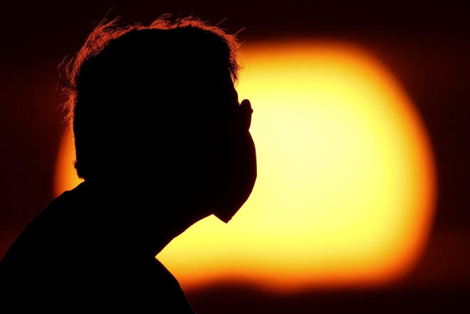 A man wearing a face mask to help prevent the spread of the coronavirus watches the sunset from a park in Kansas City, Mo..