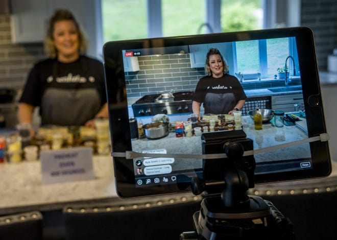 A screen displays the image of Carol Haynes as she leads a live online cooking class from the kitchen in her Mackinaw home.