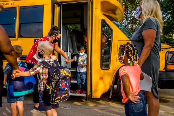 Valeska Hinton Early Childhood Education Center principal Katie Cobb, right, stands with one child in hand as others depart a bus to start the school year Wednesday, July 22, 2020. The opening for the 3-5-year-olds is the first school to open in the district and included multiple defensive measures against COVID-19 including masks required on premises, multiple entrances to the building temperature testing of all entering the building.