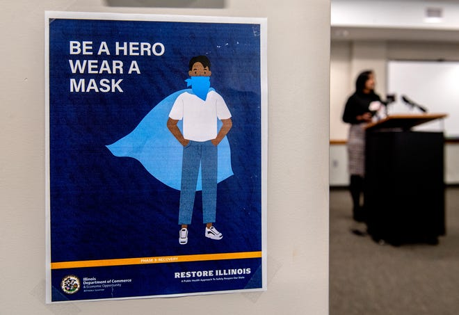 A sign urging residents to wear face masks hangs from a beam as Monica Hendrickson, public health administrator, leads a press conference updating the COVID-19 situation in the Peoria area Thursday, Oct. 1, 2020 at the Peoria City/County Health Department.