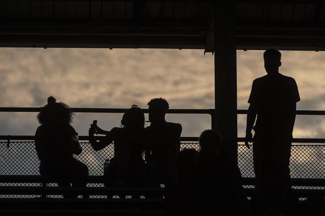 Manual fans are silhouetted by the evening sky during a football game at Peoria Stadium.